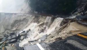 two-lane road collapsed with water cascading down the rim from the hill above