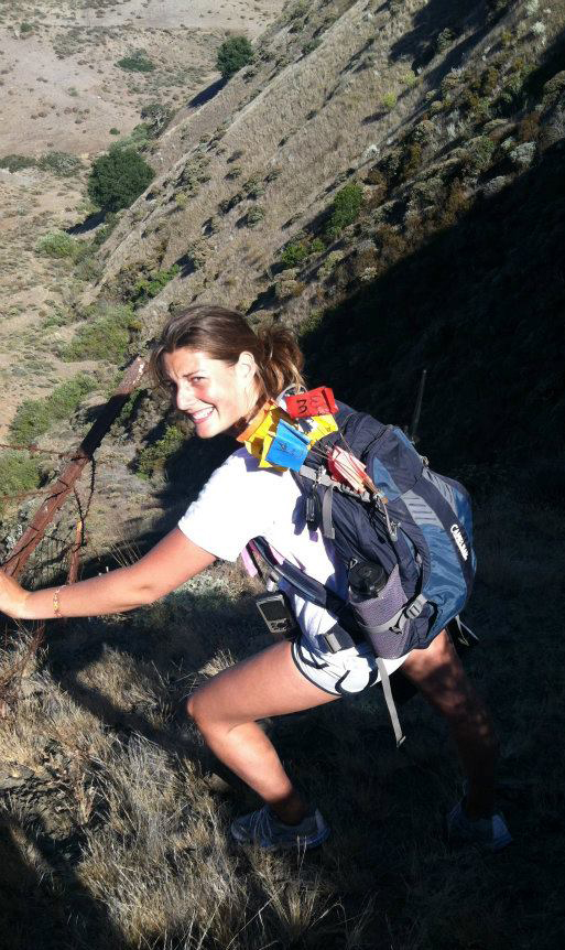 student grips barbed wire fence while walking down steep hillside